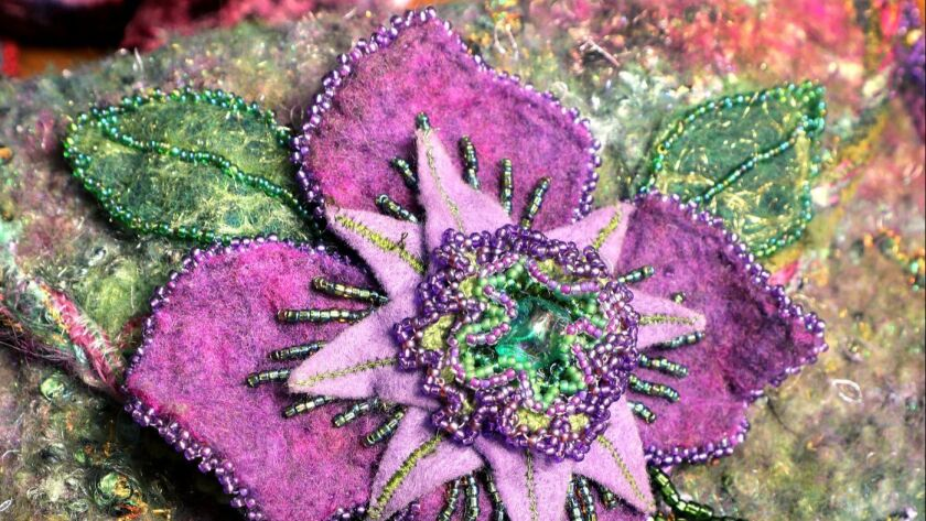 Detail view of a purse created by Rita Zerull from handmade felt and decorated with floral beading.