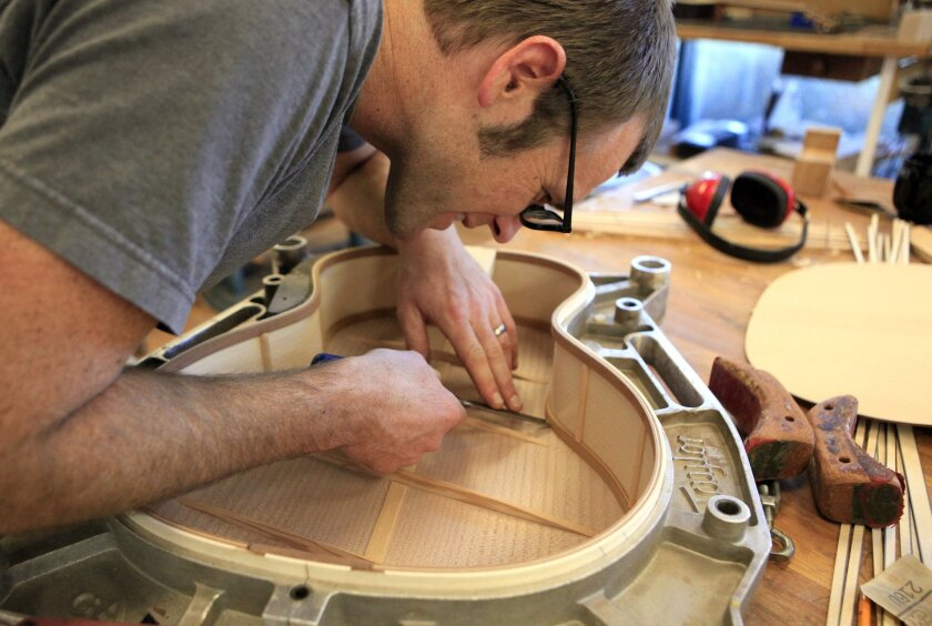 Luthier Andy Powers works on the bracing of guitar top in his Taylor guitars workshop.