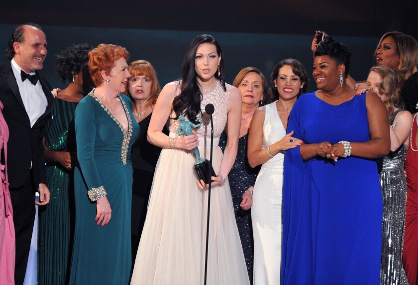 "FILE - In this Jan. 30, 2016 file photo, Laura Prepon, center, and the cast and crew of ""Orange is the New Black"" accept the award for outstanding ensemble in a comedy series at the 22nd annual Screen Actors Guild Awards at the Shrine Auditorium & Expo Hall in Los Angeles. In one of the exhaustive and damning reports on diversity in Hollywood, a new study finds that the films and television produced by major media companies are ""whitewashed,"" and that an ""epidemic of invisibility"" runs top to bottom through the industry for women, minorities and LGBT people. A study to be released Monday, Feb. 22, 2016, by the Media, Diversity and Social Change Initiative at the University of Southern California's Annenberg School for Communication and Journalism offers one of the most wide-ranging examinations of the film and television industries, including a pointed ""inclusivity index"" of 10 major media companies - from Disney to Netflix - that gives a failing grade to every movie studio and most TV makers. (Photo by Vince Bucci/Invision/AP, File)"