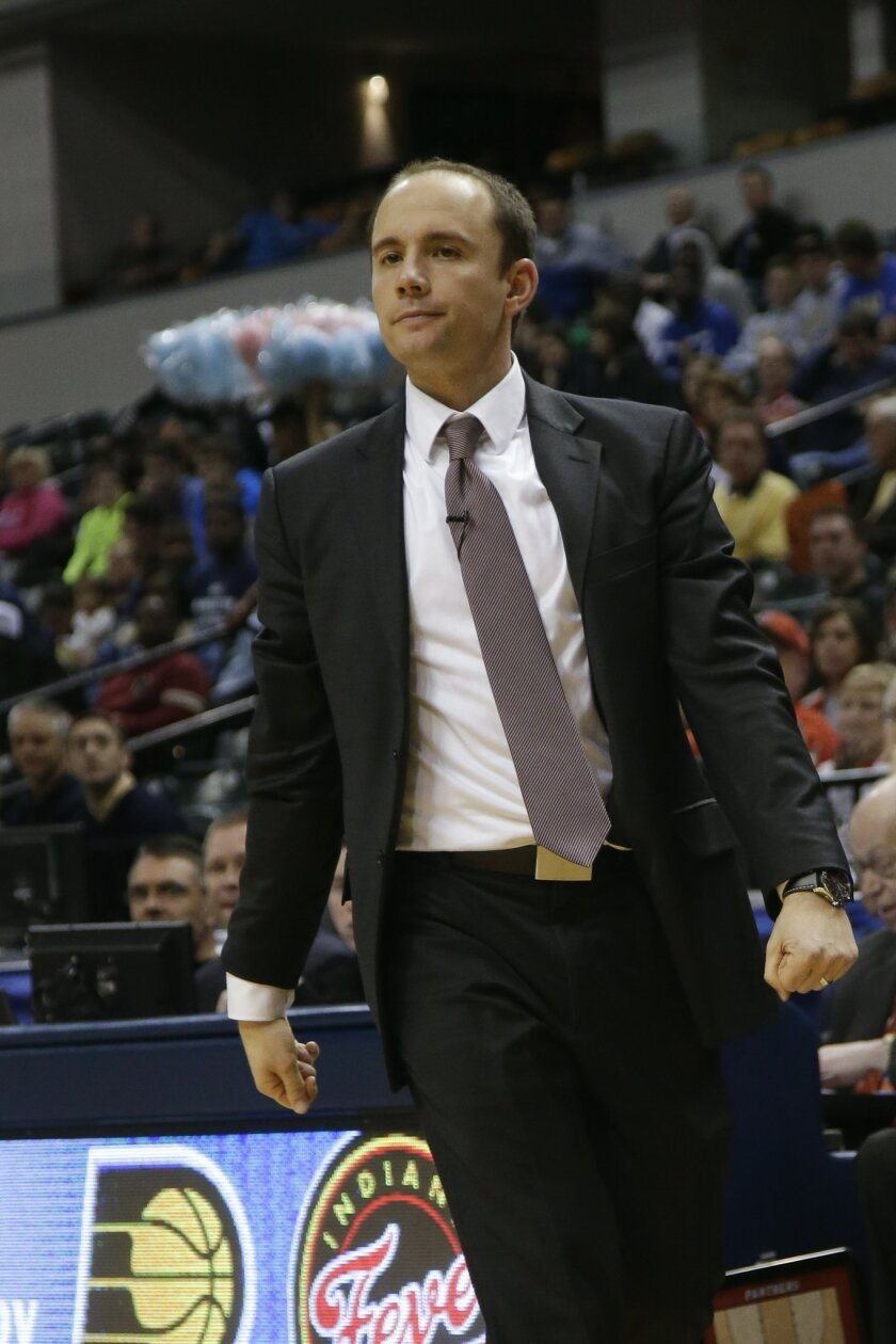 In this March 29, 2014 photo, Park Tutor coach Kyle Cox attends the IHSAA Class 2A Indiana state boys' basketball championship game in Indianapolis. Federal prosecutors have charged the former boys basketball coach at the exclusive private school with trying to entice a 15-year-old female student i