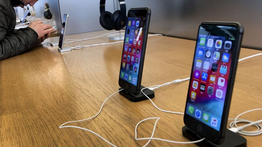 A man tries out a latest iPhone next to iPhone 8 and 8 Plus on display for sale at an Apple Store in