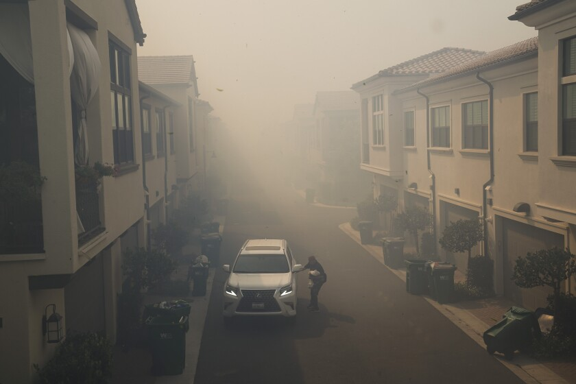 A man leaves his home during a mandatory fire evacuate as smoke from the Silverado Fire fills the air, Monday, Oct. 26, 2020, in Irvine, Calif. (AP Photo/Jae C. Hong)