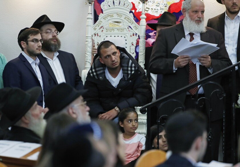 FILE - In this Monday, April 29, 2019 file photo, Almog Peretz, center, sits near his niece, Noya Dahan, 8, Monday, April 29, 2019, as they attend the funeral for Lori Kaye, who was killed Saturday when a gunman opened fire inside the Chabad of Poway synagogue in Poway, Calif. Peretz and Dahan were both injured in the shooting. Peretz, who was wounded in the shooting at the synagogue is suing the house of worship, alleging Chabad of Poway didn't use federal funds meant to hire security to protect worshipers. In the lawsuit obtained by Los Angeles Times, Peretz claims the synagogue did not have proper security despite a rise in anti-Semitic attacks nationally and that it did not use a $150,000 grant to upgrade safety measures. (AP Photo/Gregory Bull, File)