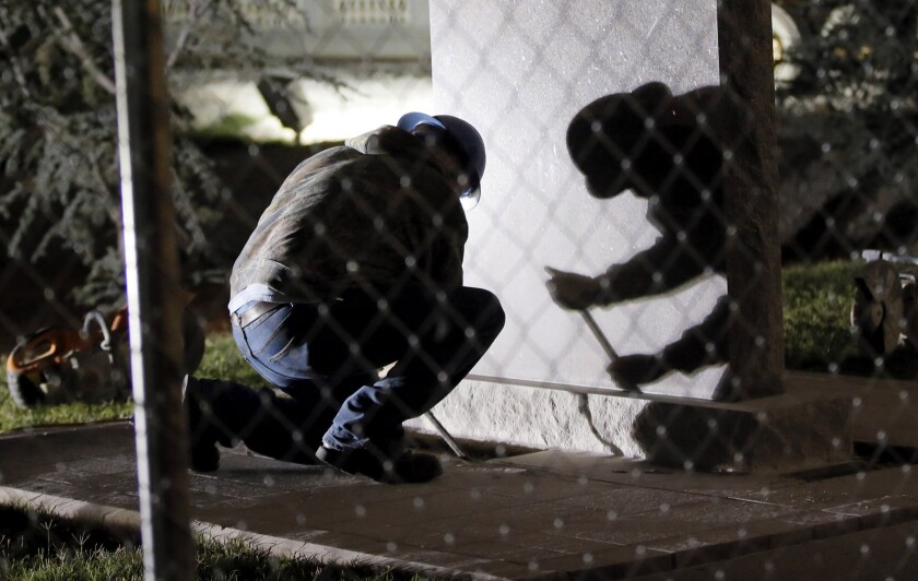 A worker pries at the base during the removal of the Ten Commandments monument from the state Capitol in Oklahoma City.