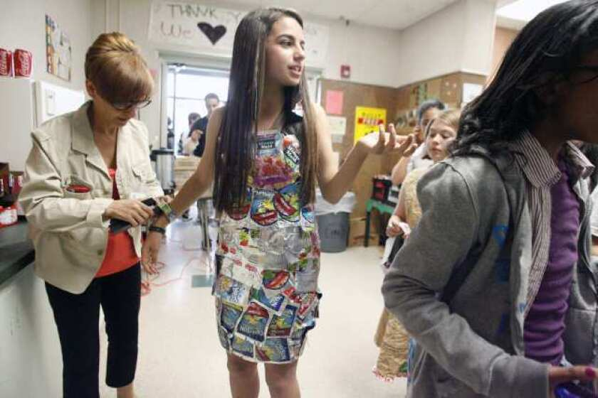 Mona Bitar, 13, middle, wears a Capri Sun dress while Mary Monsaour , left, helps Bitar with her bracelet during the Trashin' Fashion event, which took place at John Muir Middle School in Burbank on Friday. Eighth graders are fundraising for their eighth grade party and are trying to raise at least $2,000.