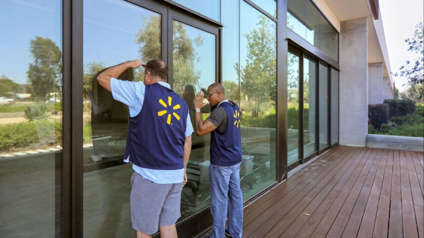 Bob Lowell, at left, and Claude Jones, at right, both Senior Directors of Engineering for Walmart Labs, try to get a view through the front windows of Walmart Labs' San Diego area offices under construction in the Make campus in Carlsbad.