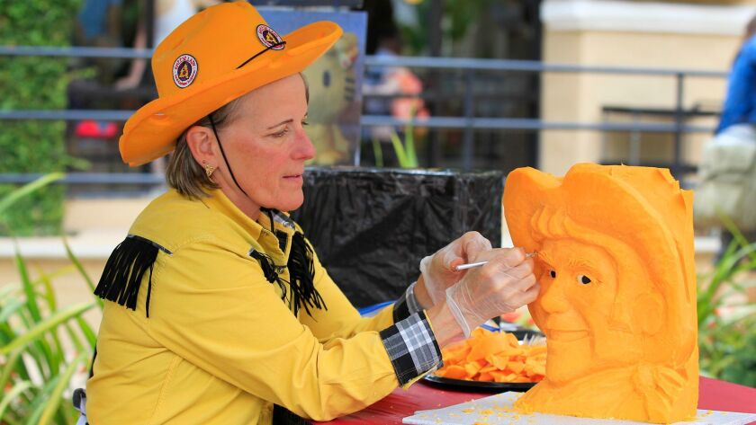 Sarah Kaufmann, of Coronado, known as The Cheese Lady carves a cowboy out of a block of cheddar cheese at the San Diego County Fair.
