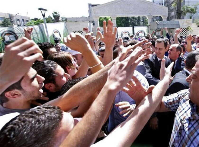 "This photo released on the official Facebook page of Syrian President Bashar Assad, shows Syrian president Bashar Assad, right, surrounded by bodyguards as young people, wave at him during the inauguration ceremony on Saturday of a statue dedicated to ""martyrs"" from Syrian universities who died in the country's two-year-old uprising and civil war, in Damascus, Syria, Saturday, May. 4, 2013. Assad's second public appearance in a week came as Israeli officials confirmed the country's air force car"