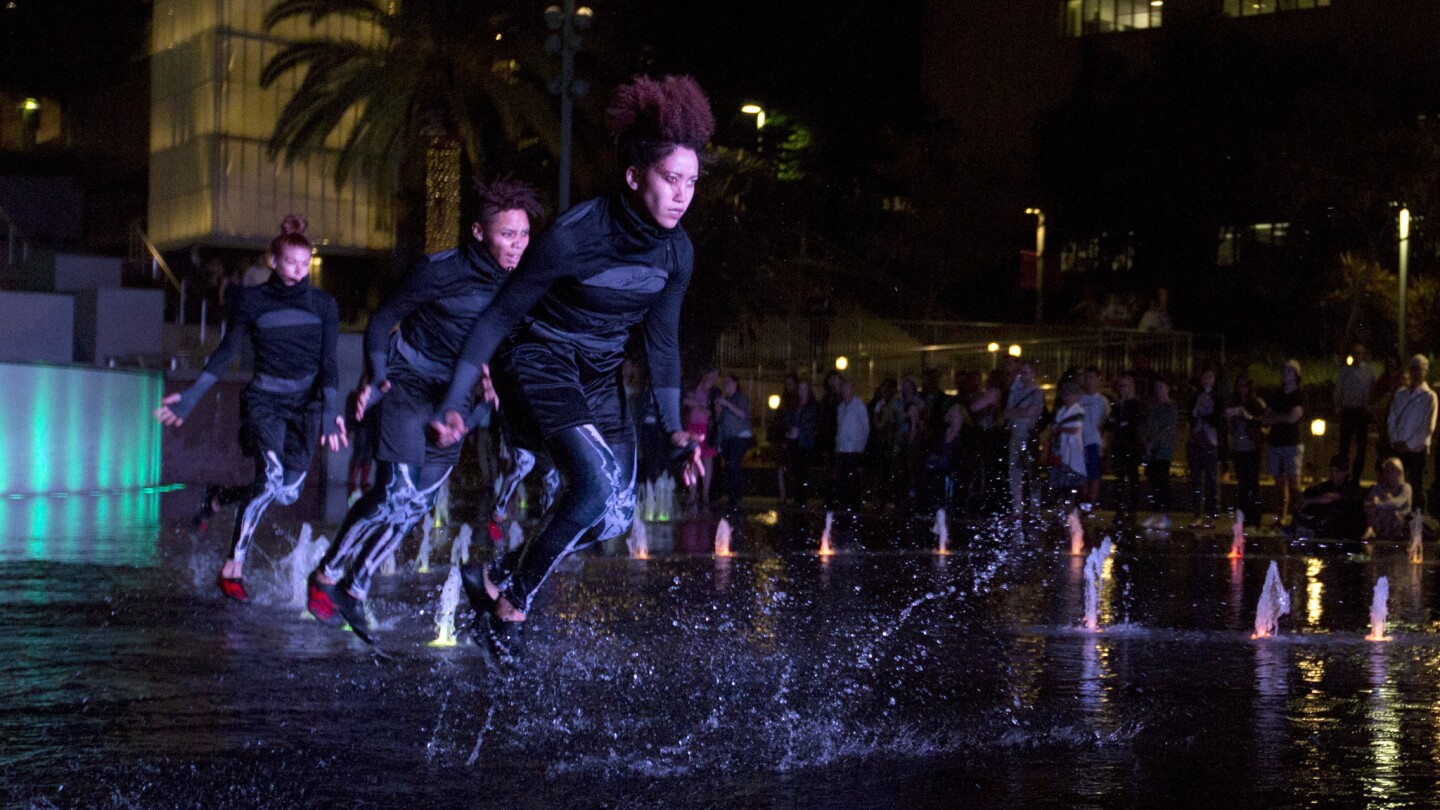 """Dancers from Decadancetheatre perform """"The Firebird"""" in the fountain in Grand Park on Monday, the Music Center's opening night of its contemporary dance program Moves After Dark."""