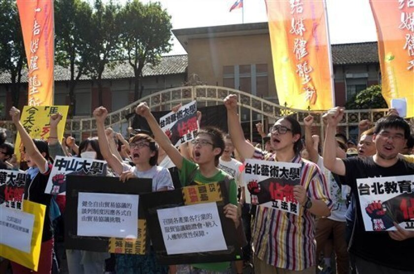 """Student protesters shout slogans against Taiwan's latest trade pact agreement with China outside of the legislature, in Taipei, Taiwan, Wednesday, July 31, 2013. The pact, signed between the sides on June 21, allows each to invest in the other's service sectors, including banking. Signs read """"Occup"""