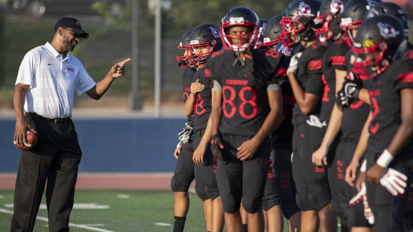 Village Christian offensive line coach Todd McNair talks with players on the field in Burbank on Friday.