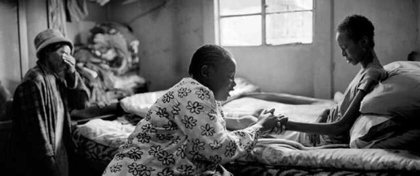 Maria Vindi, left, prays with her mother and volunteer Forget Gutuza, who provides needed assistance.