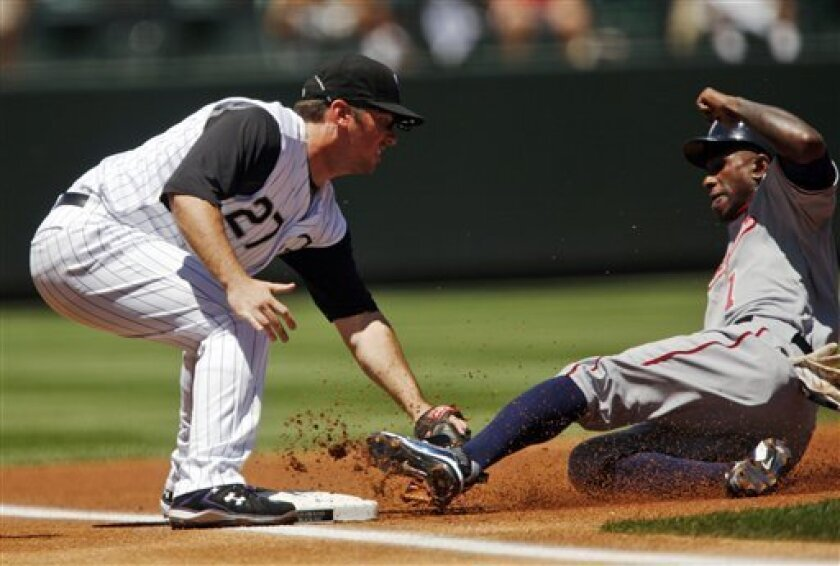 Colorado Rockies third baseman Garrett Atkins, left, tags out Washington Nationals' Nyjer Morgan as he tried to advance from first to third base on single hit by Alberto Gonzalez during the first inning of a baseball game in Denver on Wednesday, July 8, 2009. (AP Photo/David Zalubowski)