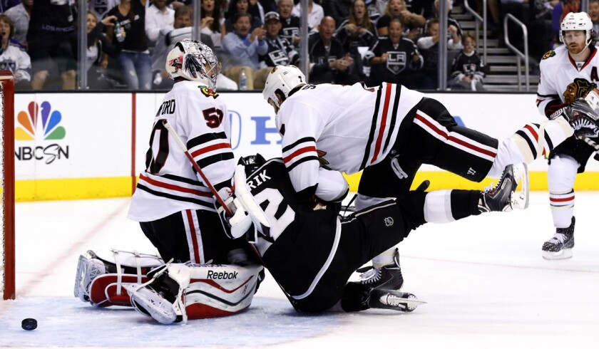 Kings forward Marian Gaborik is taken down by Blackhawks defenseman Brent Seabrook after re-directing the puck past goaltender Corey Crawford for a goal in the first period of Game 4 on Monday night at Staples Center.