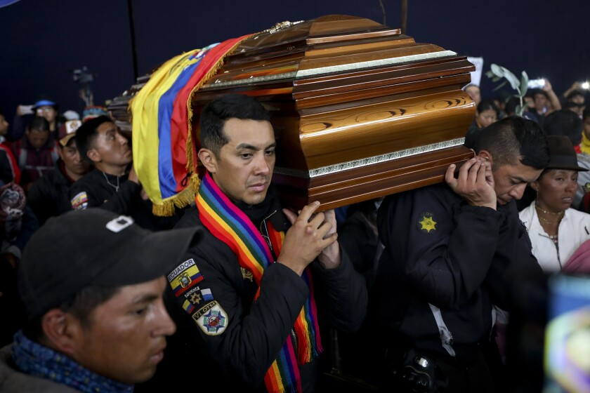 Police held captive by anti-government protesters, are forced to carry a coffin that contain the remains of a companion who protesters say died during yesterday's national strike, in a procession inside the Casa de Cultura in Quito, Ecuador, Thursday, Oct. 10, 2019. An indigenous leader and four other people have died in unrest in Ecuador since last week, the public defender's office said Thursday. (AP Photo/Fernando Vergara)