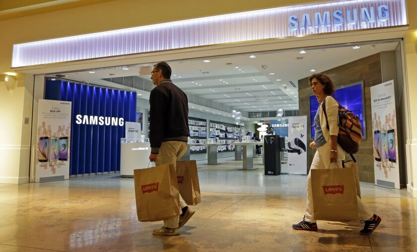 In this photo taken Tuesday, Feb. 9, 2016, shoppers walk by a Samsung store in Miami. On Friday, July 15, 2016, the Commerce Department releases U.S. retail sales data for June. (AP Photo/Alan Diaz)
