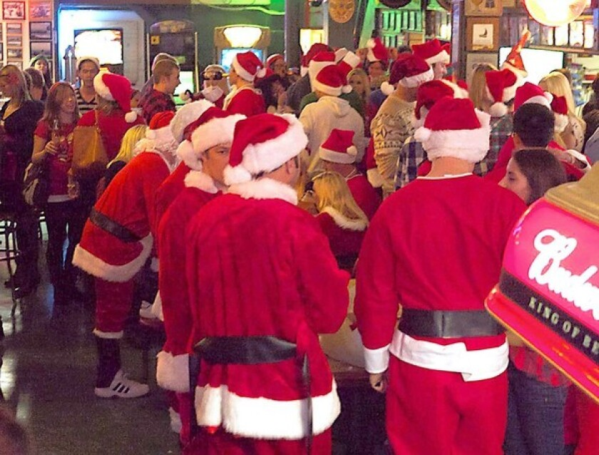 Dozens of Balboa pub crawlers dress in Santa outfits Saturday night in order to raise awareness and funds for Project Access, a charity for low-income families.