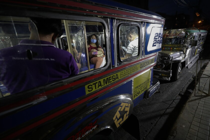 Passengers wait inside a traditional Jeepney bus fitted with plastic sheets to separate passengers as part of health measures to help prevent the spread of the new coronavirus in metropolitan Manila, Philippines on Friday, July 3, 2020. The government is allowing some routes for Jeepneys to be opened to help public transportation as the government slowly eases the coronavirus lockdown (AP Photo/Aaron Favila)