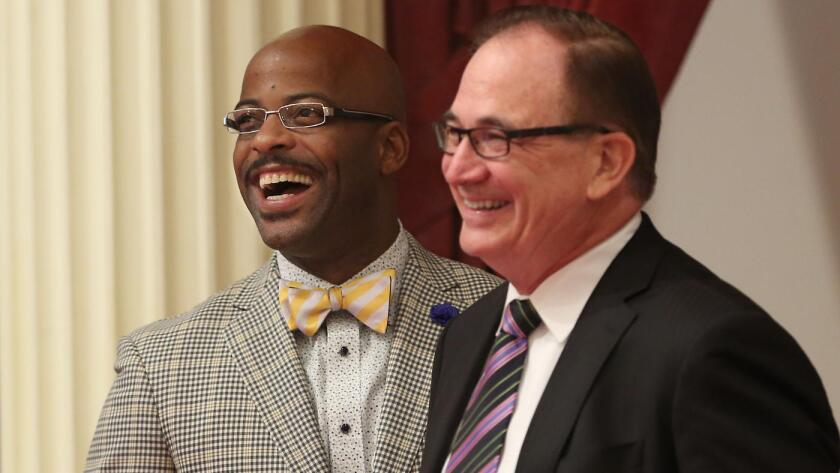 Assemblyman Isadore Hall (D-Compton), left, and Senate Minority Leader Robert Huff (R-Diamond Bar) smile as Hall's measure seeking to ban California from selling or displaying items with the Confederate flag was approved by the Senate on Monday.