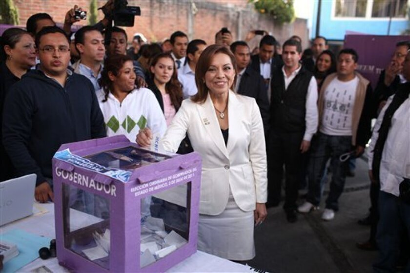 Josefina Vasquez Mota, center, presidential candidate of Mexico's National Action Party, PAN, casts her vote during the party's primary elections in Huixquilucan, Mexico, Sunday, Feb. 5, 2012. If nominated Vasquez Mota would be the first woman for a major political party to run for Mexico's highest office. (AP Photo/Alexandre Meneghini)