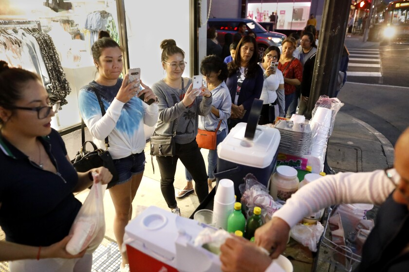 Customers wait in line for Andres Santos' esquites