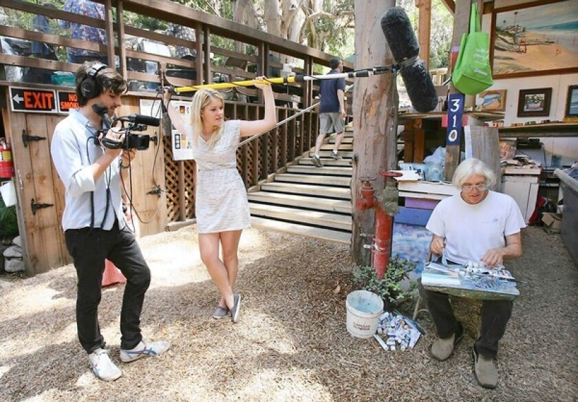 """Cameraman Rich Costales and producer Kailee McGee film longtime exhibitor Doug Miller in action for thier documentary about the Sawdust Festival """"The Dust."""""""