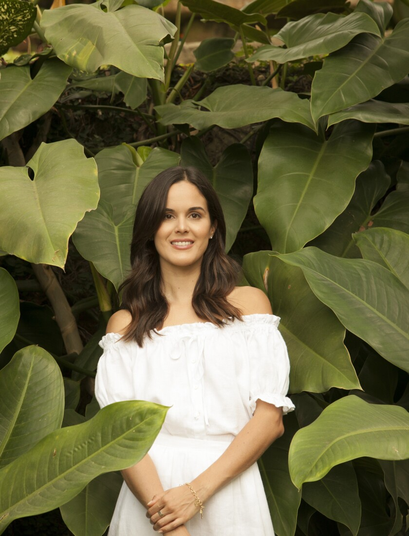 A woman in a white off-the shoulders dress stands surrounded by tropical foliage.