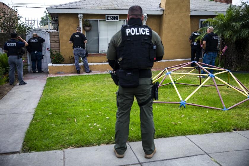 LYNWOOD, CALIF. - JUNE 10: Immigration and Customs Enforcement fugitive operations team members knoc