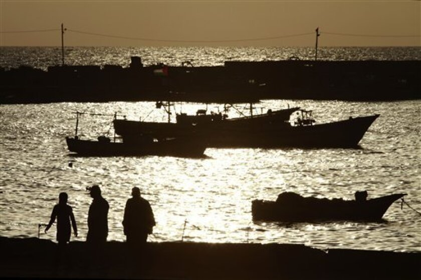 Palestinians walk at the Gaza City port, Monday June 7, 2010. The Israeli navy killed four Palestinian militants in diver suits off the coast of Gaza before dawn Monday, the Israeli military and Palestinian officials said. The deadly incident comes a week after nine pro-Palestinian activists were killed in a clash with naval commandos as their vessel tried to reach Gaza. The interception prompted a worldwide outcry and growing demands that Israel ease or lift its blockade of Gaza which also includes a maritime blockade that was highlighted in recent days when Gaza-bound aid ships were intercepted by the Israeli navy. (AP Photo/Lefteris Pitarakis)