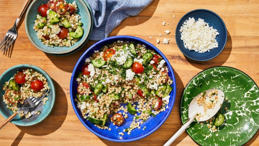Tender Israeli couscous soaks up a tart vinaigrette and plays well with crunchy, cold cucumbers, cherry tomatoes and feta. Prop styling by Nidia Cueva.