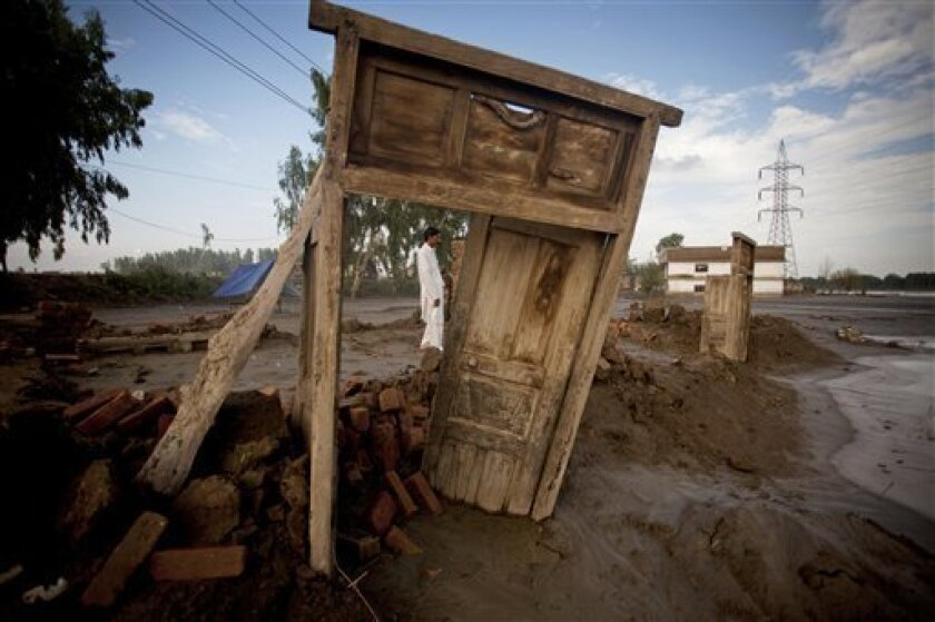 A Pakistani villager stands outside what is left of homes washed away by heavy floods in Charsadda, northwest Pakistan, Monday, Aug. 9, 2010. The number of people suffering from the massive floods in Pakistan exceeds 13 million, more than the combined total of the 2004 Indian Ocean tsunami, the 200