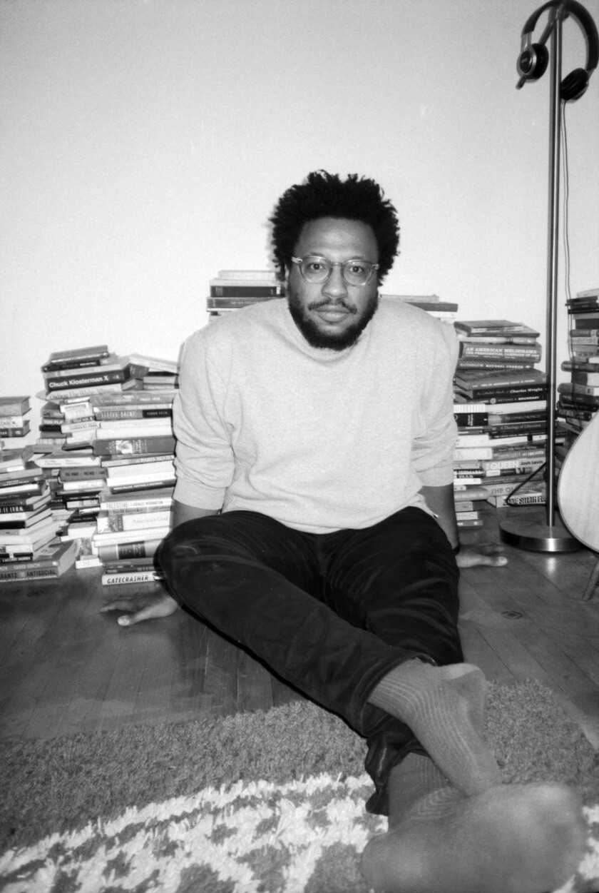 Writer Vinson Cunningham sits on the floor surrounded by books in Brooklyn.