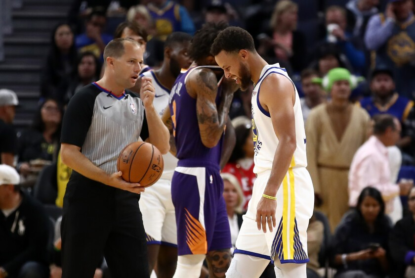 Warriors guard Stephen Curry grimaces after he fell to the court and broke his left hand during the second half of a game against the Suns at Chase Center on Oct. 30, 2019 in San Francisco.