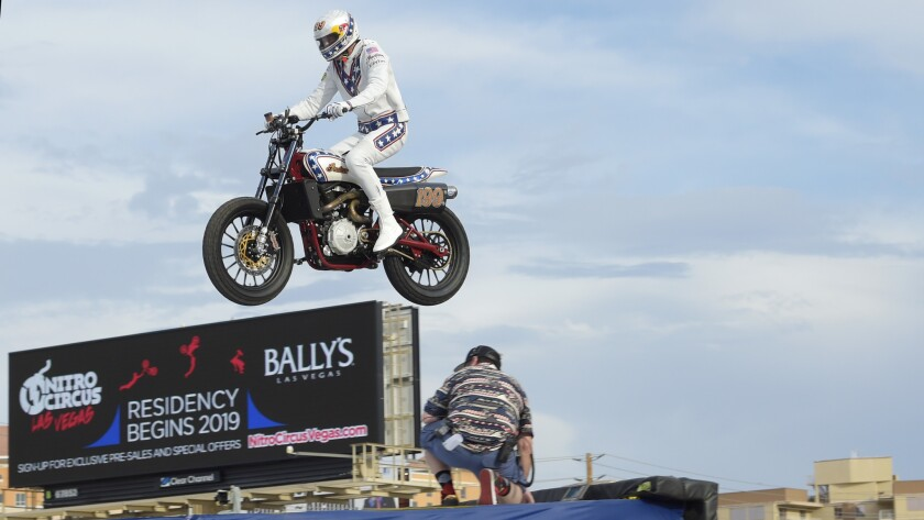 Travis Pastrana jumps his motorcycle over 52 cars as he attempts to make three of Evel Knievel's his
