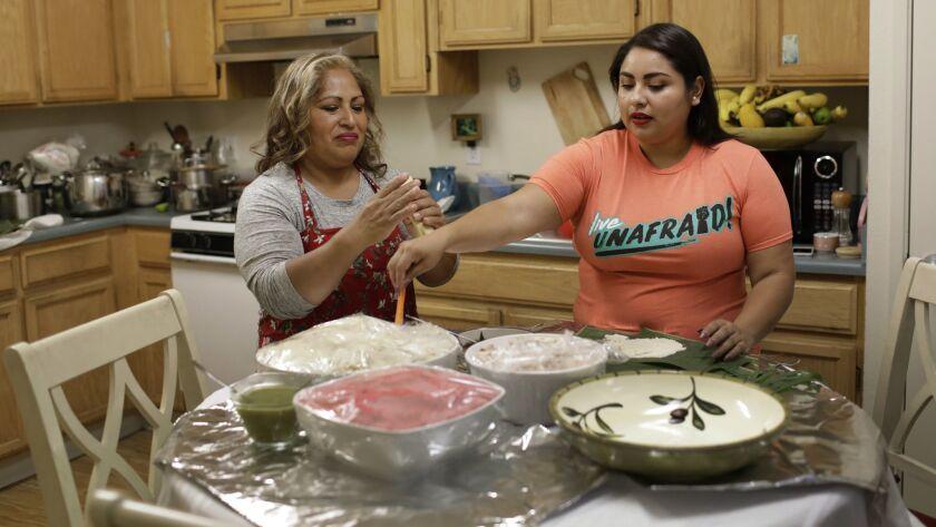 SANTA CRUZ, CA-DECEMBER 16, 2018: Gabriela Cruz, right, and her mother, Irma Cruz, left, make tamale