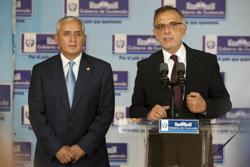 Ivan Velasquez, of the United Nations International Commission Against Impunity, right, speaks with reporters, accompanied by Guatemala's President Otto Perez Molina, during a press conference at the National Palace in Guatemala City, Thursday, April 23, 2015. Perez Molina said Thursday that he is seeking another two-year renewal of the commission investigating criminal networks. (AP Photo/Moises Castillo)