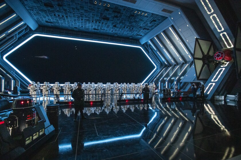 A member of the First Order and 50 Stormtroopers stand guard next to a TIE fighter in the hangar bay of the First Order Star Destroyer during a media preview Thursday.