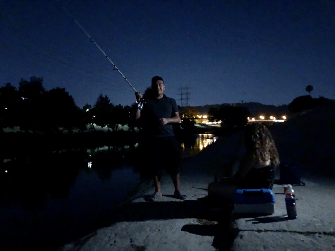 Alex Mendoza fishes with a friend after sunset.