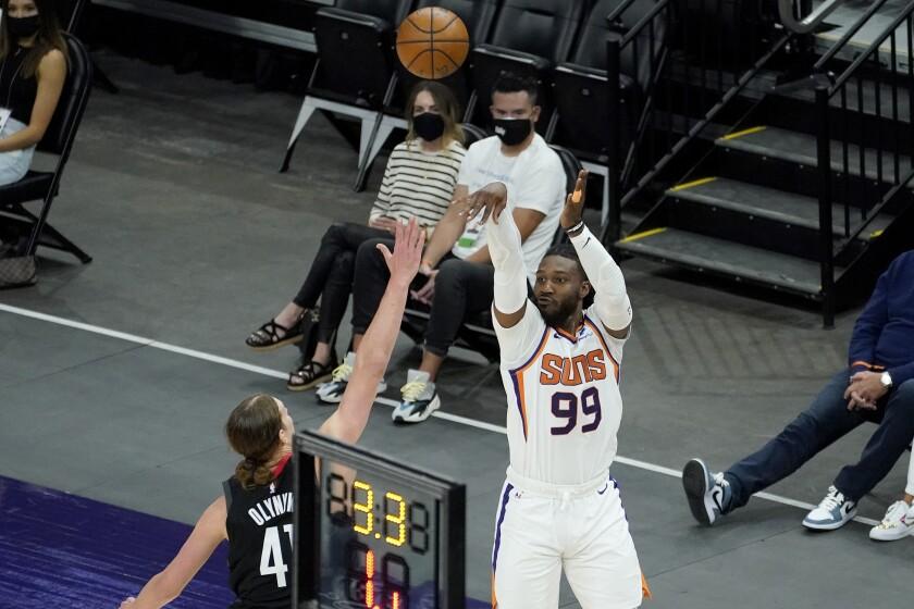 Phoenix Suns forward Jae Crowder (99) shoots a three pointer over Houston Rockets forward Kelly Olynyk during the first half of an NBA basketball game, Monday, April 12, 2021, in Phoenix. (AP Photo/Matt York)
