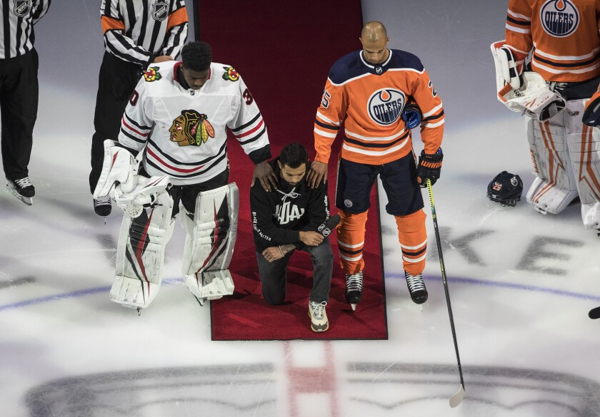 Matt Dumba takes a knee during the U.S. national anthem flanked by Oilers' Darnell Nurse and Blackhawks' Malcolm Subban