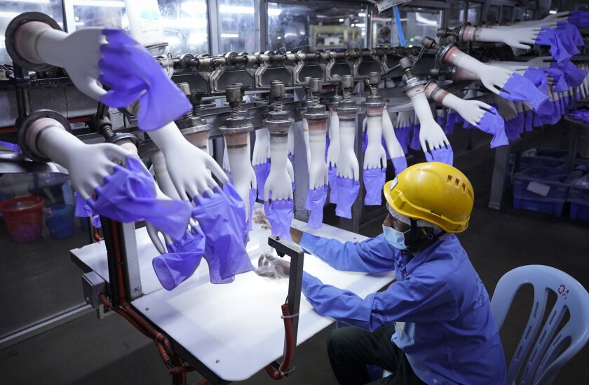 FILE - In this Aug. 26, 2020, file photo, a worker inspects disposable gloves at the Top Glove factory in Shah Alam outside Kuala Lumpur, Malaysia. Malaysia's Top Glove Corp., the world's largest rubber glove maker, said in May, 2021, it hopes to swiftly end a U.S. ban on its products due to allegations of forced labor after one of its shipment was seized at a U.S. port. Malaysia's government pledged Monday, July 5, 2021, to take steps to eliminate forced labor after the country was downgraded by the U.S. to the worst level in an annual report on human trafficking. (AP Photo/Vincent Thian, File)