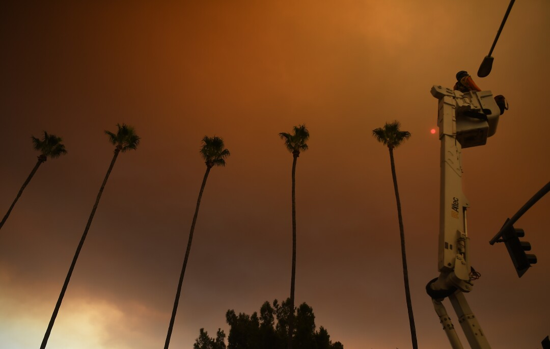 A contract worker installs a street camera to a light post along North Azuza Ave. as smoke covers the sky
