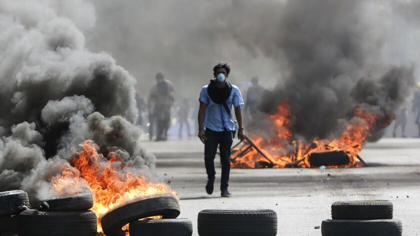 A masked protester walks between burning barricades in Managua, Nicaragua, on April 20.