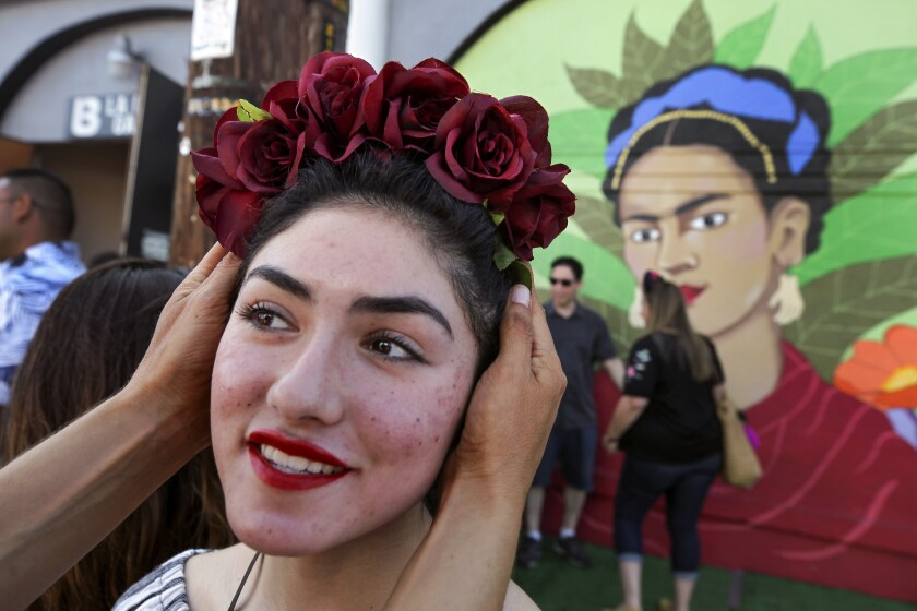 Frida Ramos, 16, stands in front of a large mural of Frida Kahlo, painted by artist and owner of the La Bodega Gallery Soni Lopez, as her mother Beatriz Ramos adjusts her flower crown during the fifth annual Friducha on Saturday.