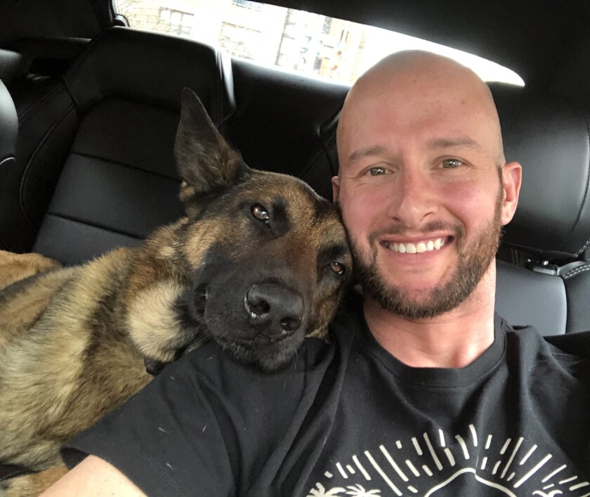 In a vehicle, Abel rests his head on the shoulder of handler Richard Pickett-White.