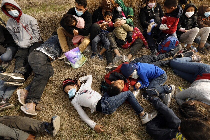 Asylum seekers detained by Border Patrol, including minors and babies, sleep on the ground while waiting over 12 hours without food and water before being bused to Border Patrol facilities for processing in south Texas. (Photo by Carolyn Cole / Los Angeles Times)
