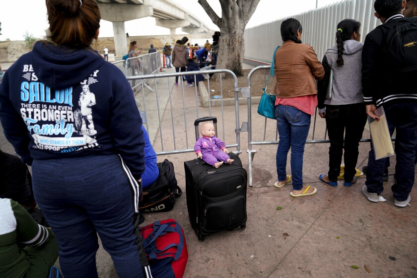 Asylum seekers wait to hear numbers called at El Chaparral