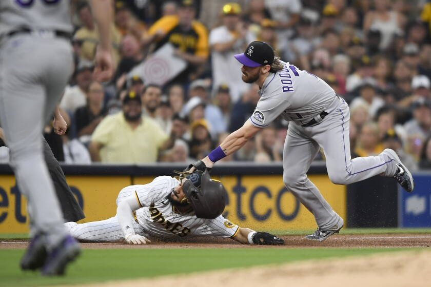 Fernando Tatis Jr. is tagged out at third base by the Rockies' Brendan Rodgers