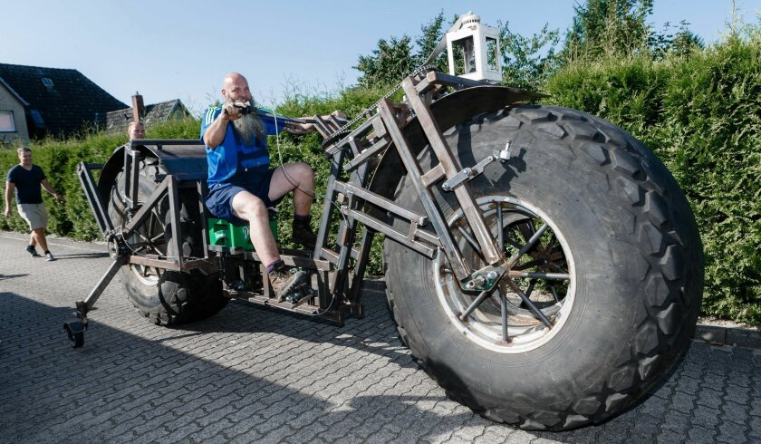In this photo taken Saturday, Aug. 27, 2016 Frank Dose for the first time rides his self made bicycle in Rade, Germany. With giant tires from an industrial fertilizer spreader and scrap steel, a Dose has built a bike weighing 940 kilograms (2,072 pound) that he plans to pedal into the record books