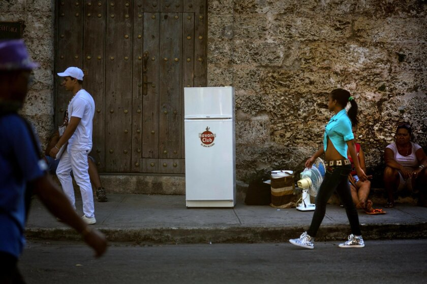 Two women sit on a sidewalk next to their refrigerator and other belongings as they wait for a moving truck to transport them to their new residence, in Havana, Cuba, Tuesday, Feb. 17, 2015. A more relaxed and hopeful atmosphere is evident in Cuba as a result of President Raul Castroís modest refor